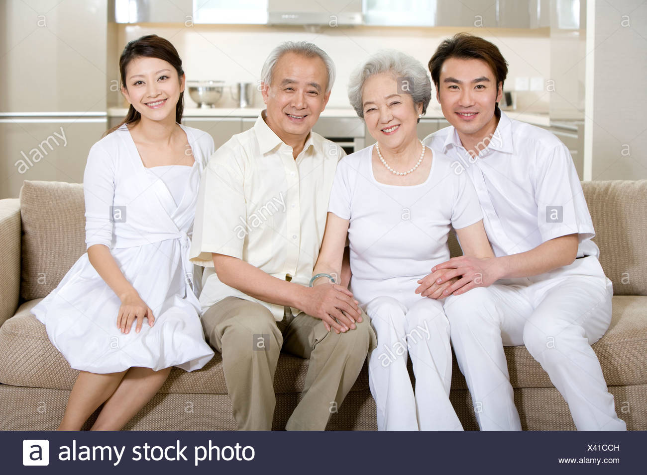 Portrait of a two generation family with adult offspring - Stock Image