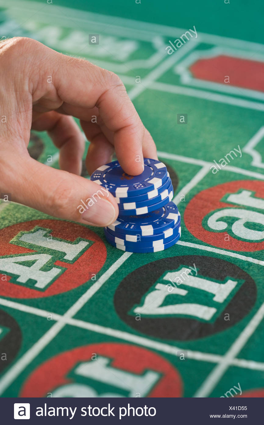 Man placing gambling chips on roulette table Stock Photo
