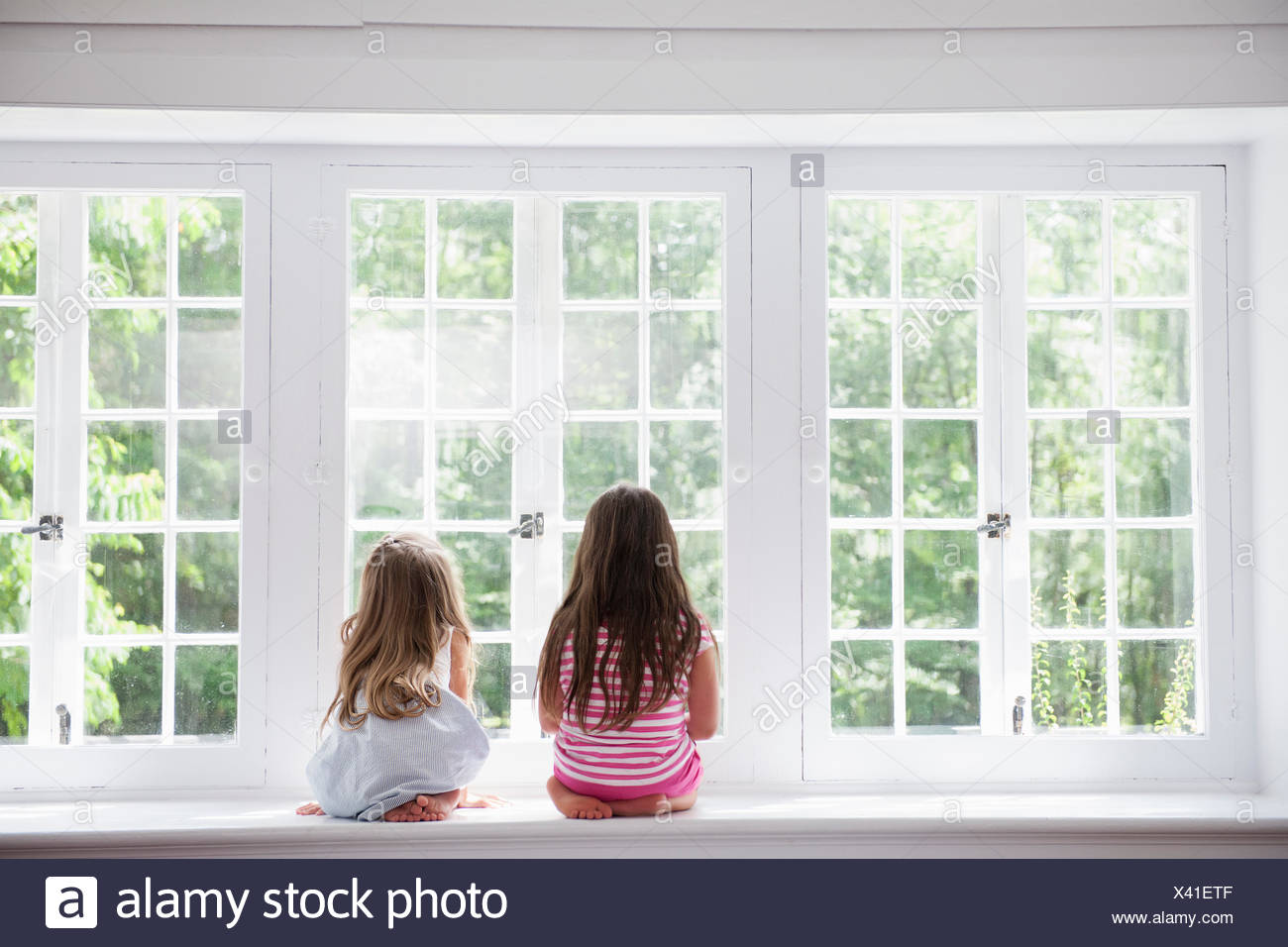 Two girls sitting side by side by a large window. - Stock Image