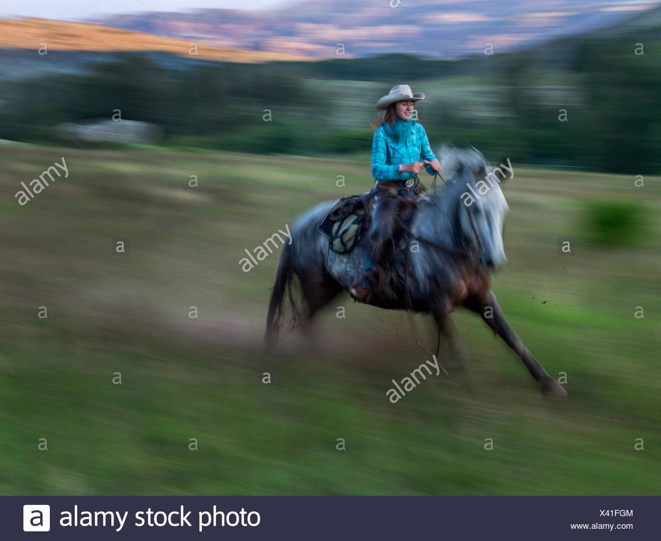 A cowgirl riding horse at the CM Ranch. - Stock Image