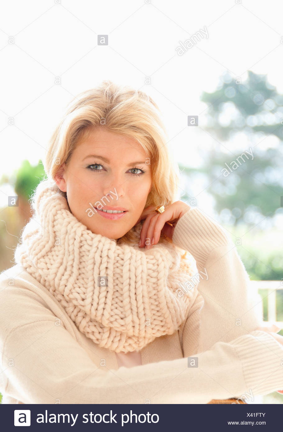 Portrait of mid adult woman in cosy jumper - Stock Image
