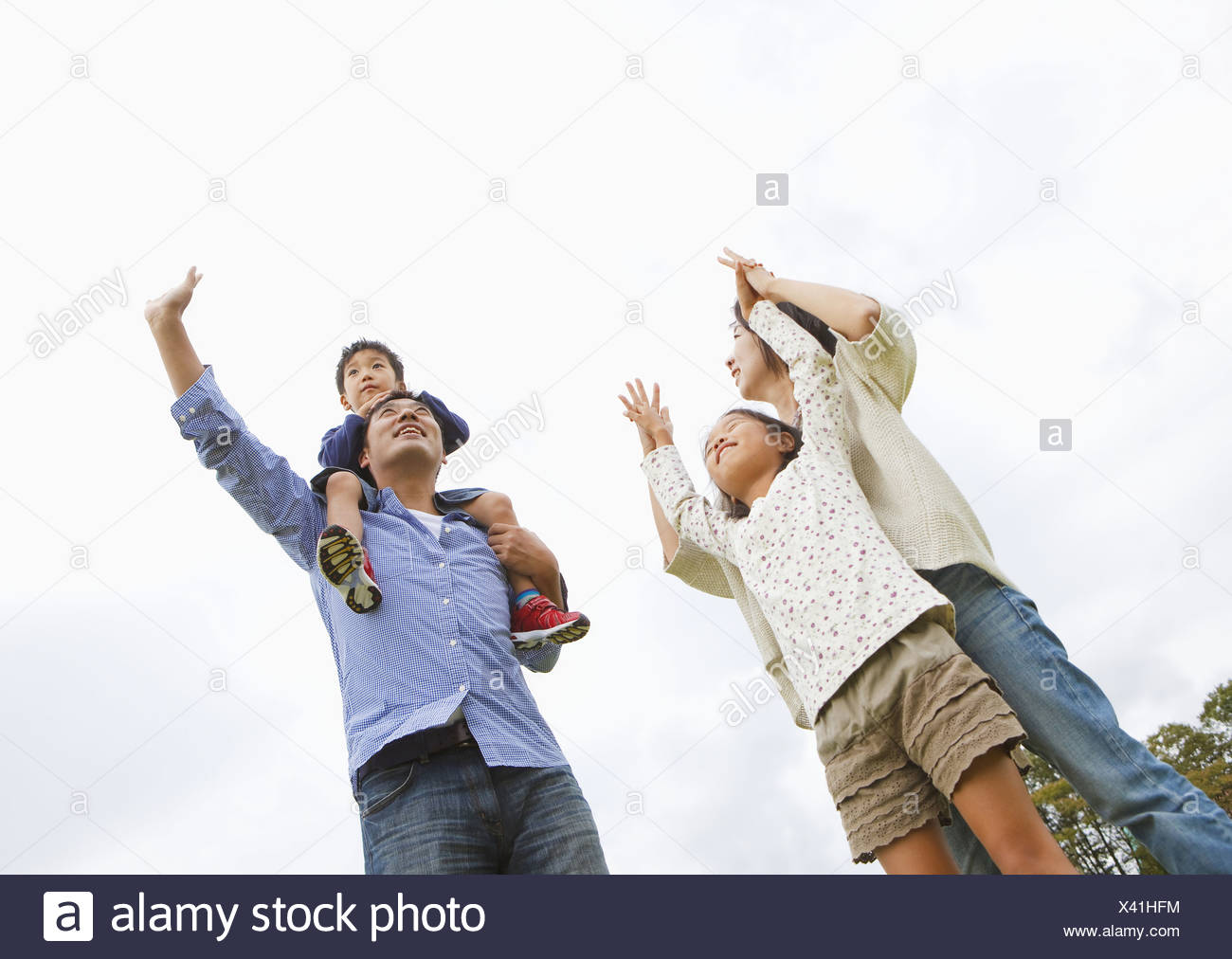 Family reaching for the sky - Stock Image