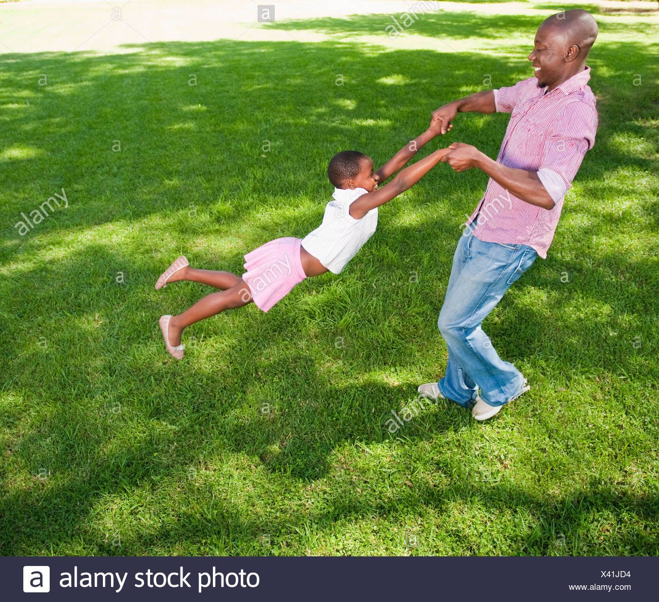 Father swinging daughter (8-9) on lawn in garden, Johannesburg, Gauteng Province, South Africa Stock Photo