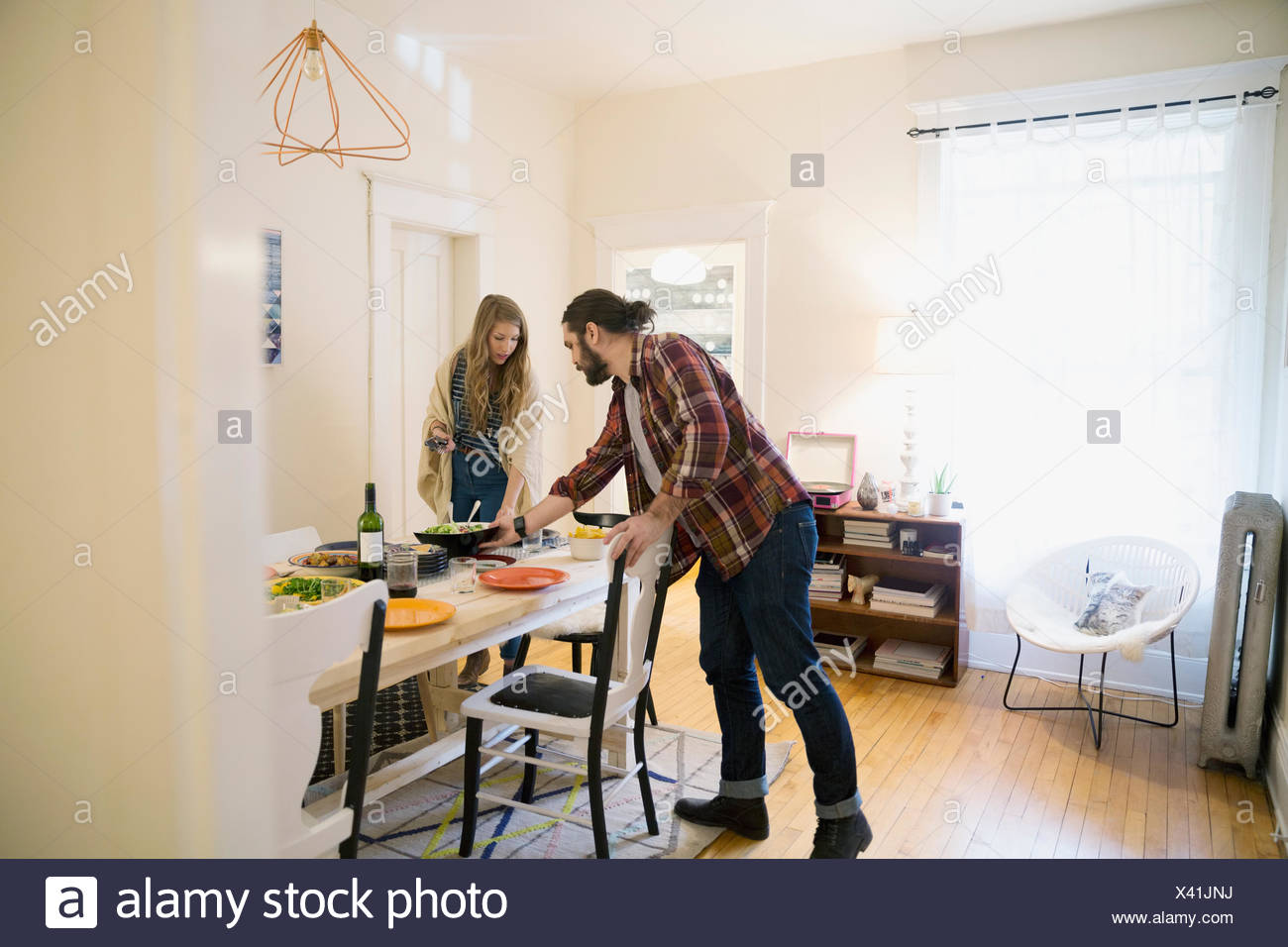 Couple setting the table in dining room - Stock Image