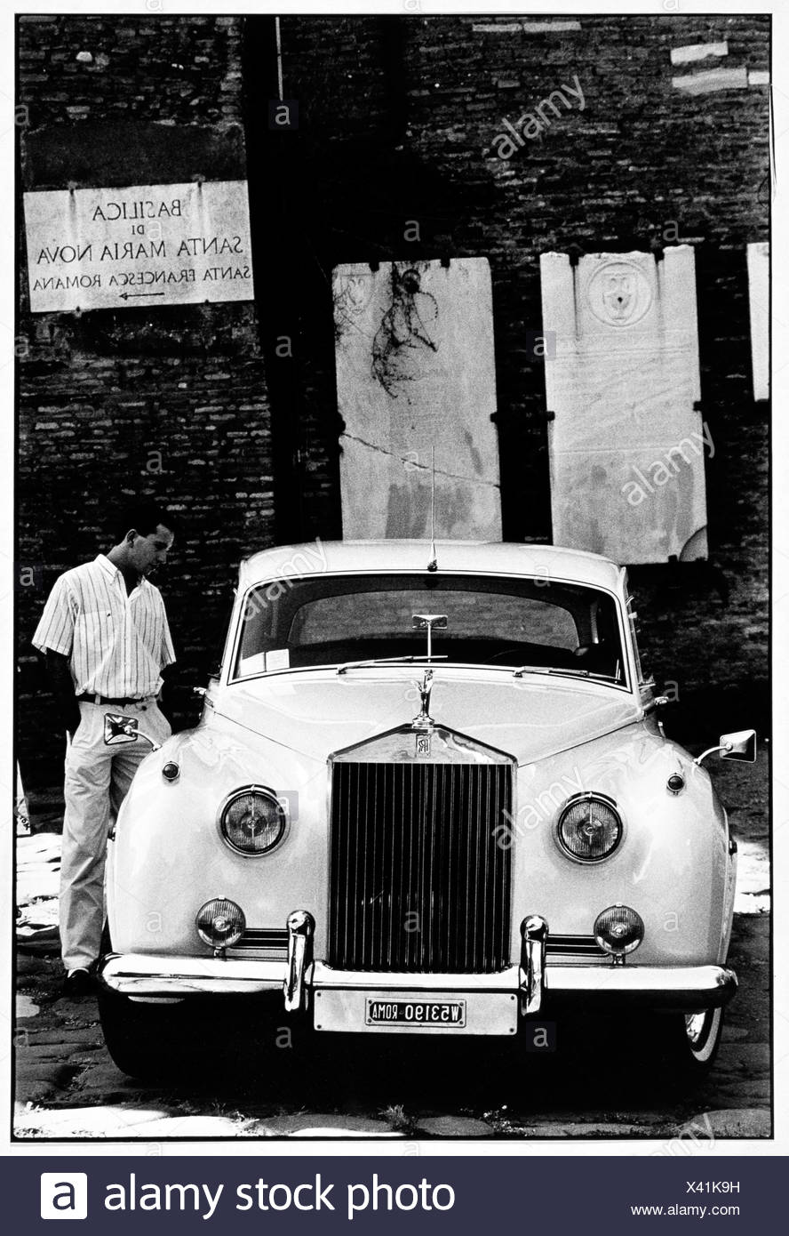 A man looks at a Rolls Royce parked in Rome. - Stock Image