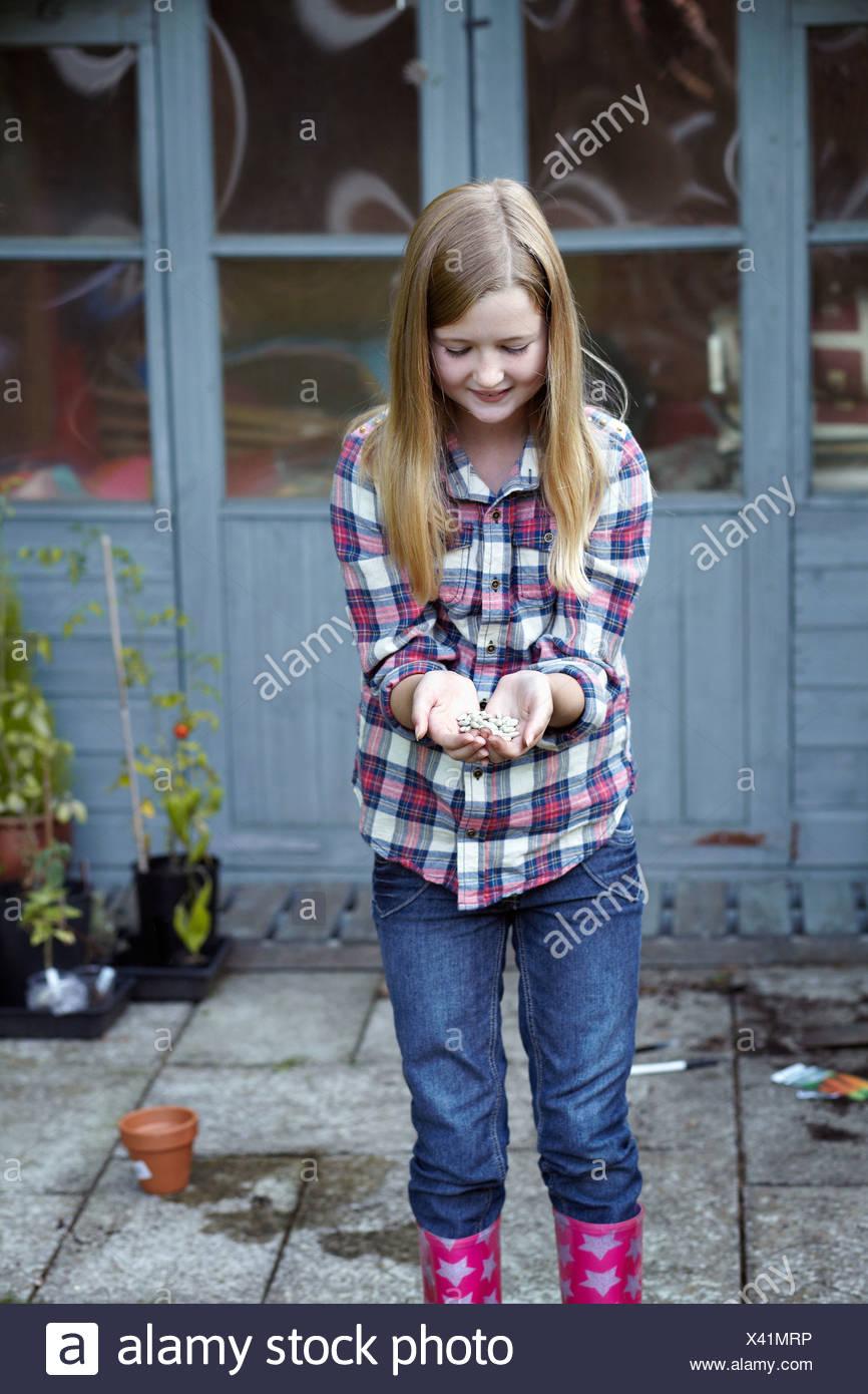 Girl in garden cupping seeds in hand - Stock Image