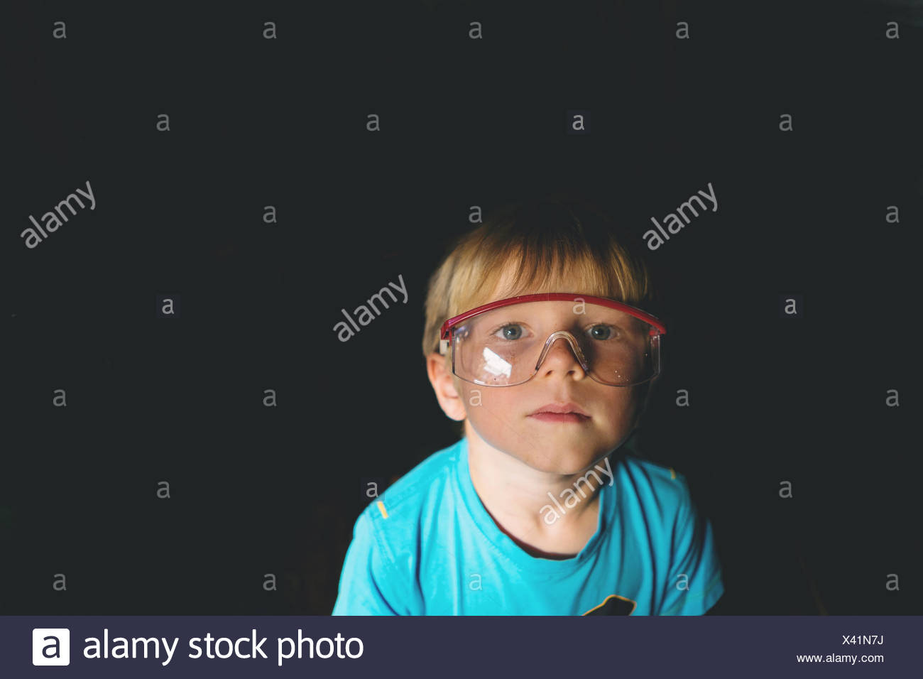 Portrait of boy wearing safety glasses - Stock Image