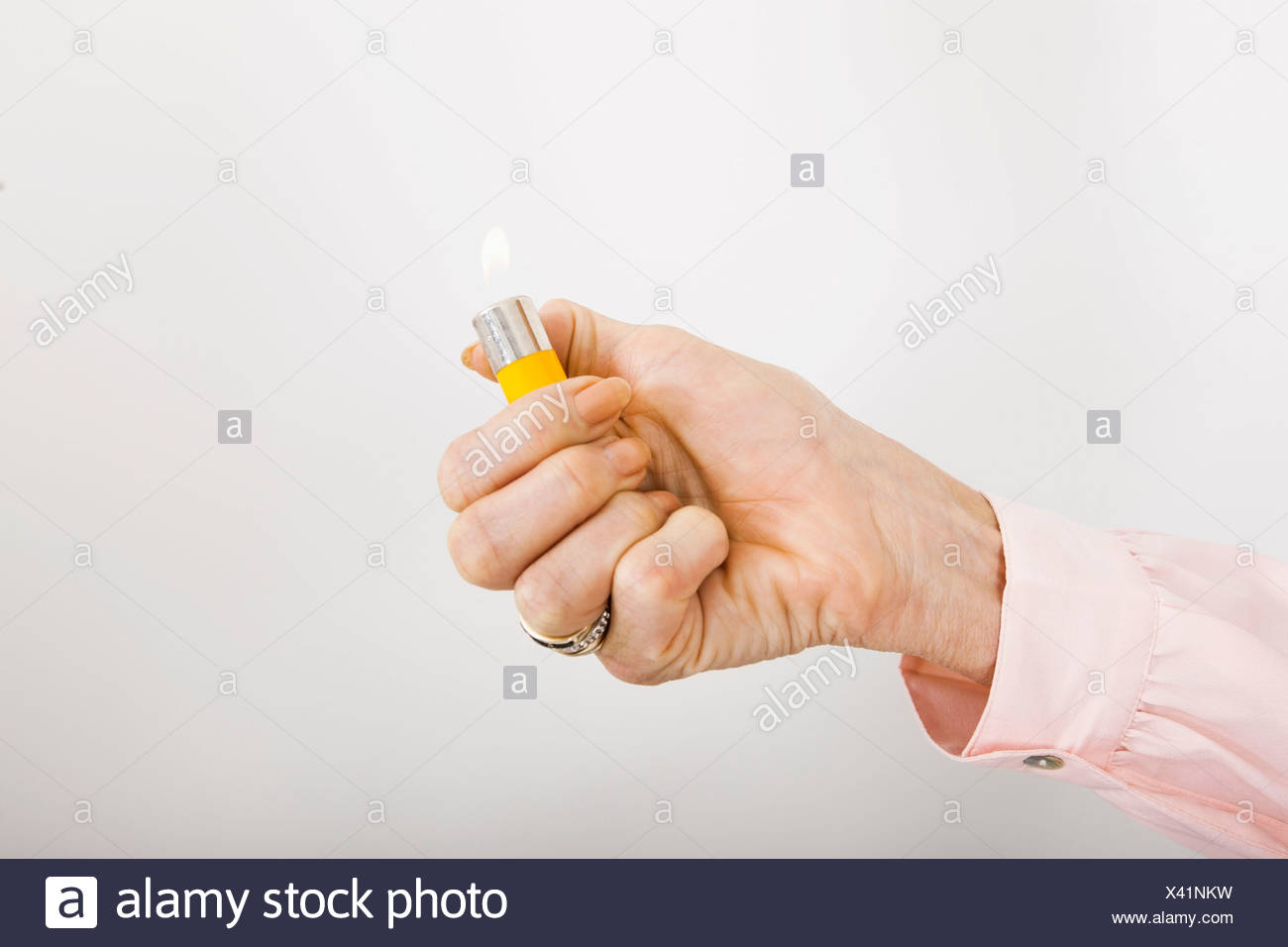 Businesswoman's hand holding cigarette lighter with flame in office - Stock Image