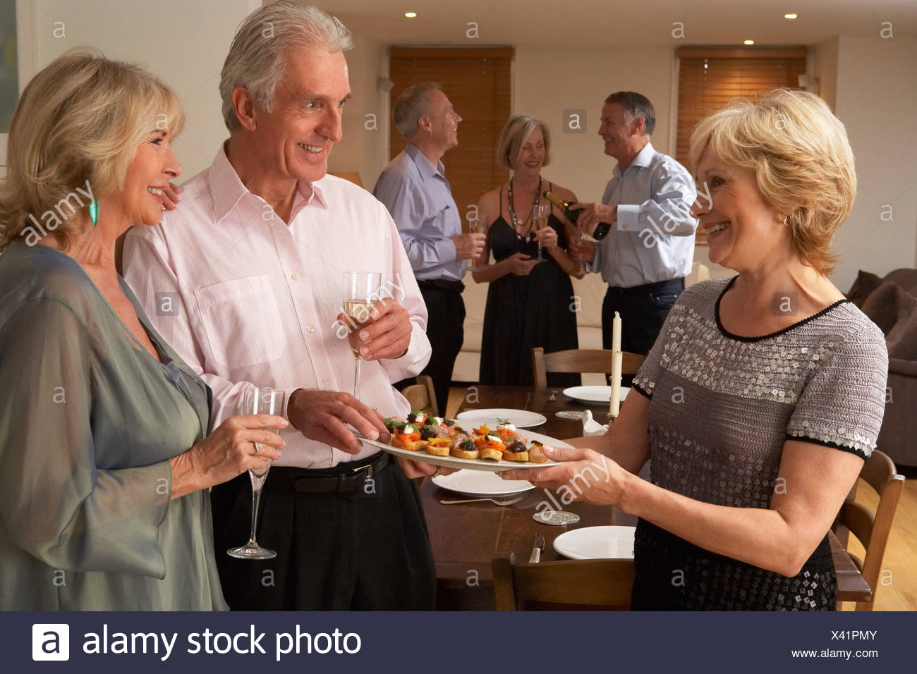 Woman Serving Hors D'oeuvres To Her Guests At A Dinner Party - Stock Image