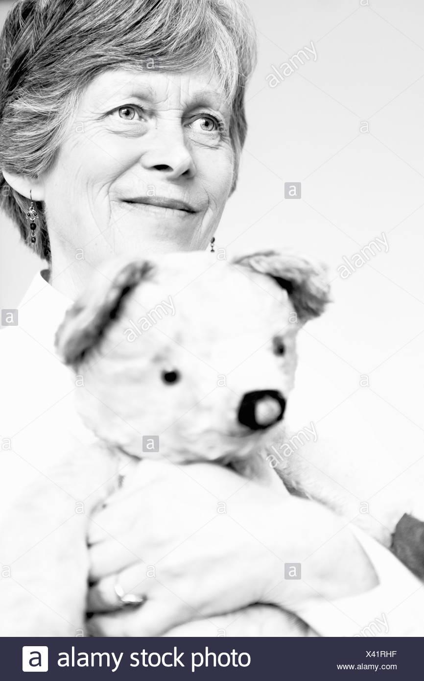 Black and white studio portrait of senior woman holding teddy bear - Stock Image