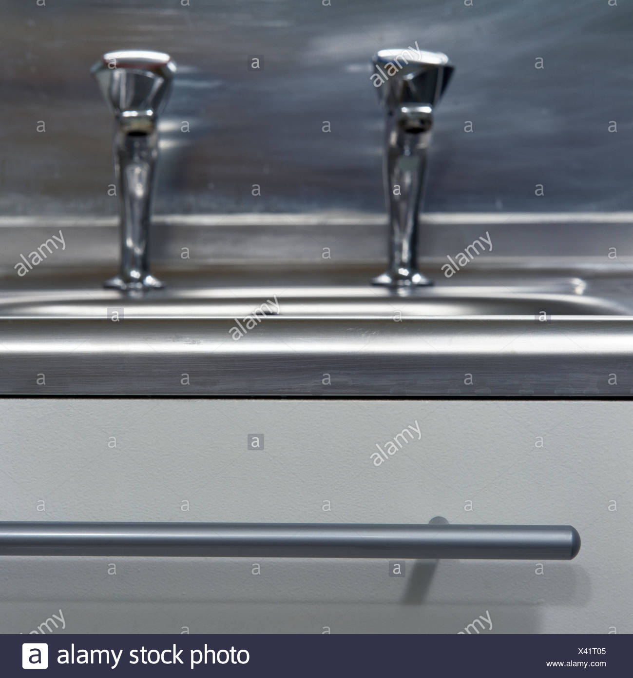 Close-up of stainless steel taps - Stock Image