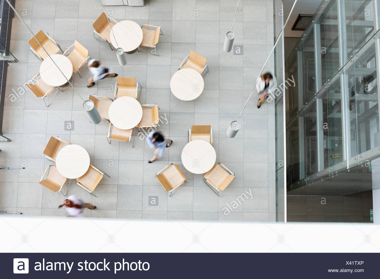 Blurred motion of businesswomen walking at office canteen - Stock Image