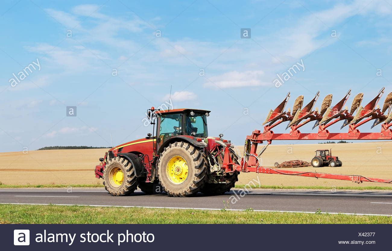 Tractor moving plough on the road - Stock Image