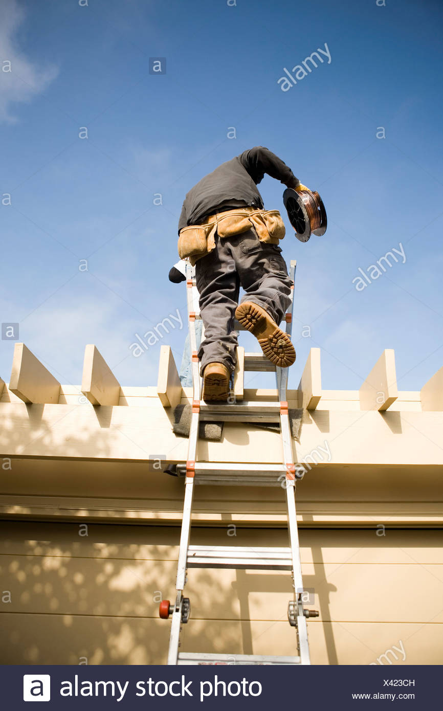 Workman on ladder to roof - Stock Image