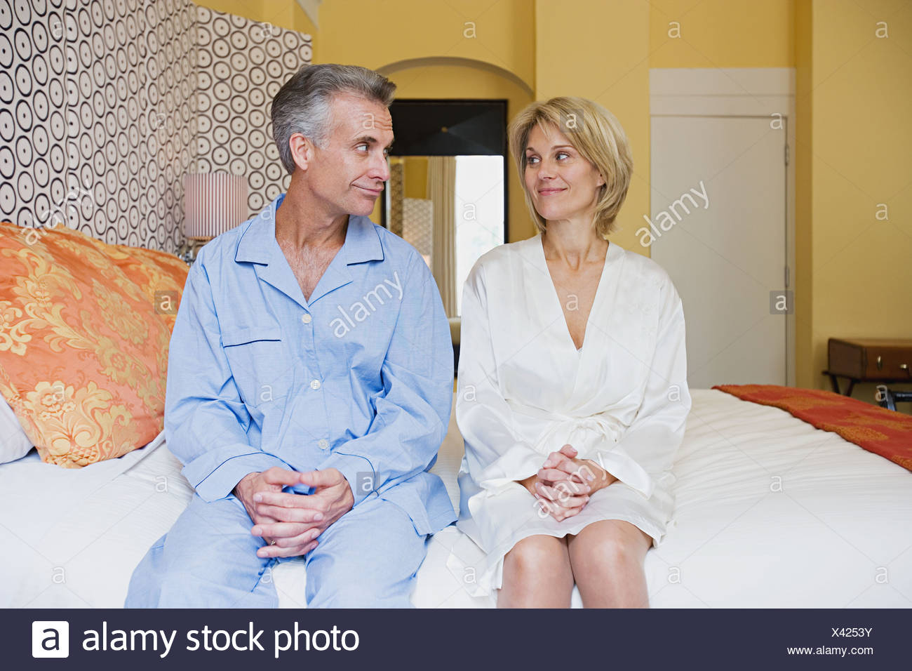 Couple sitting on bed - Stock Image