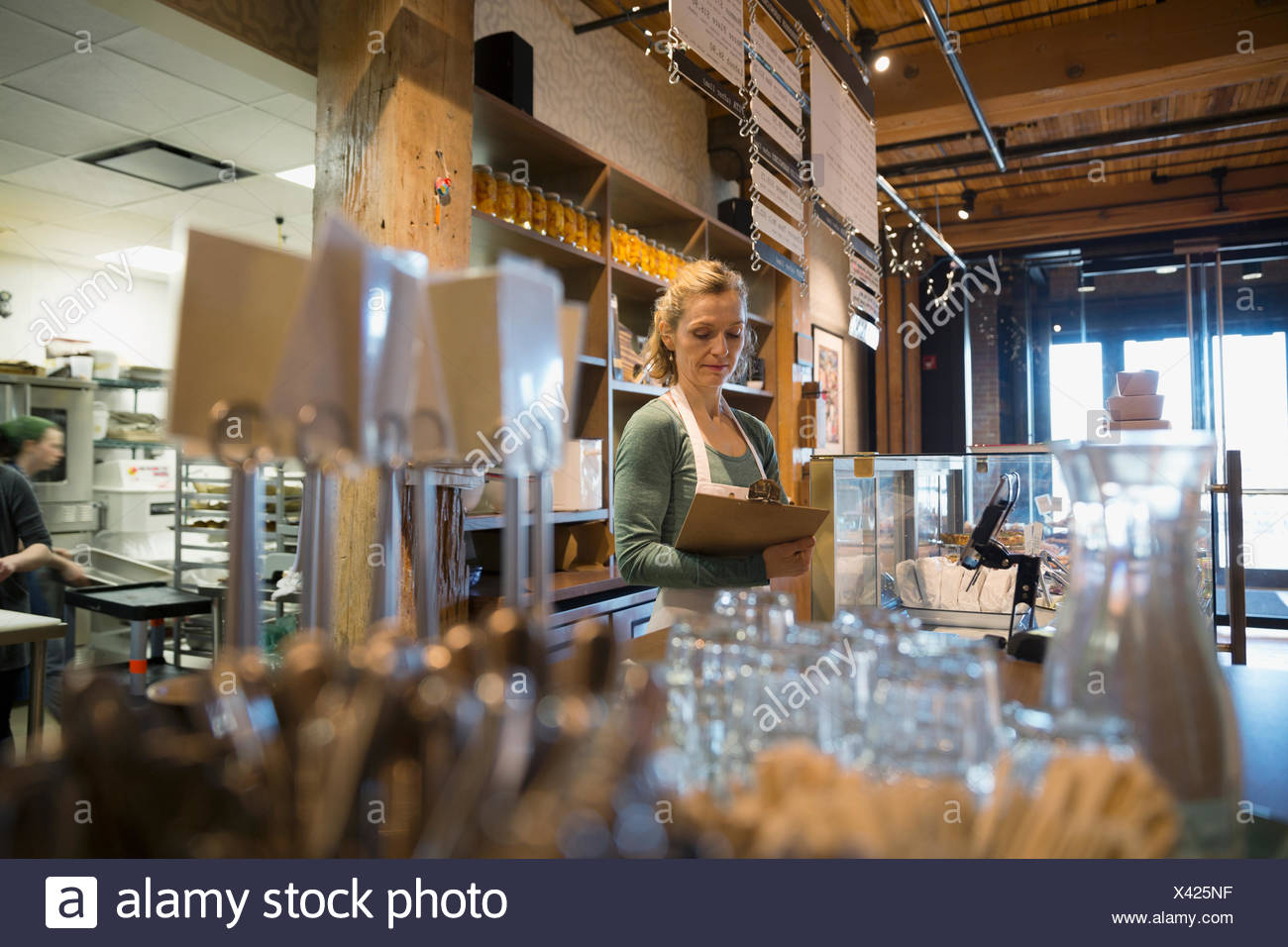 Bakery owner with clipboard behind the counter - Stock Image