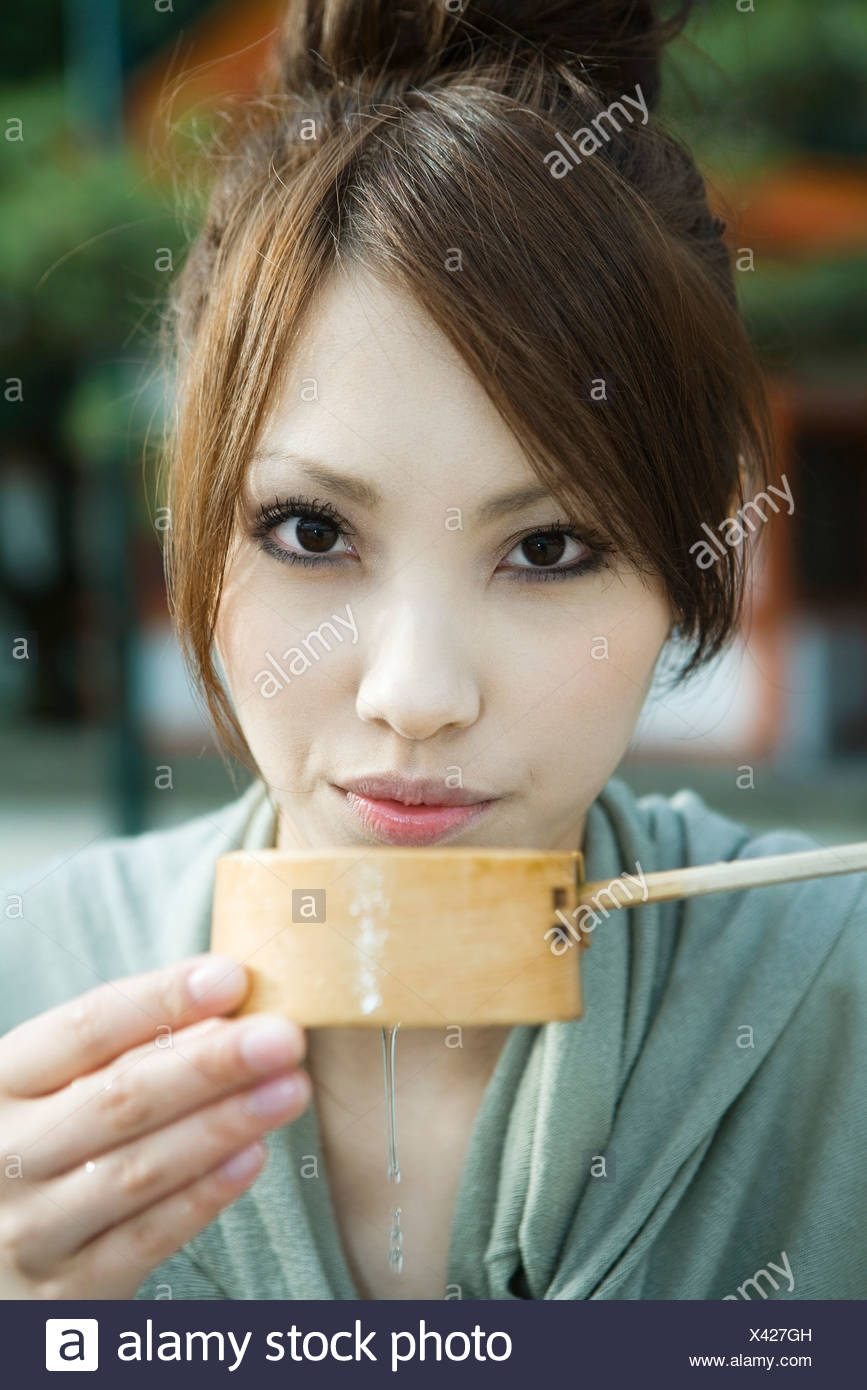 Woman drinking from traditional Japanese Hishaku ladle - Stock Image