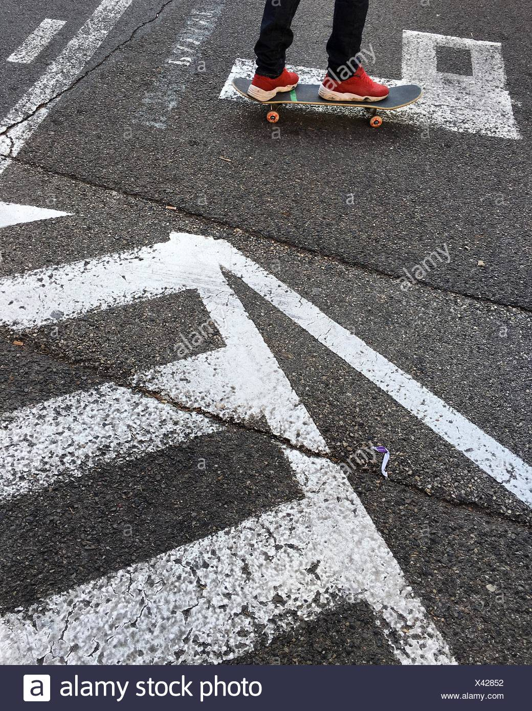 Low Section Of Man Skateboarding On Road - Stock Image