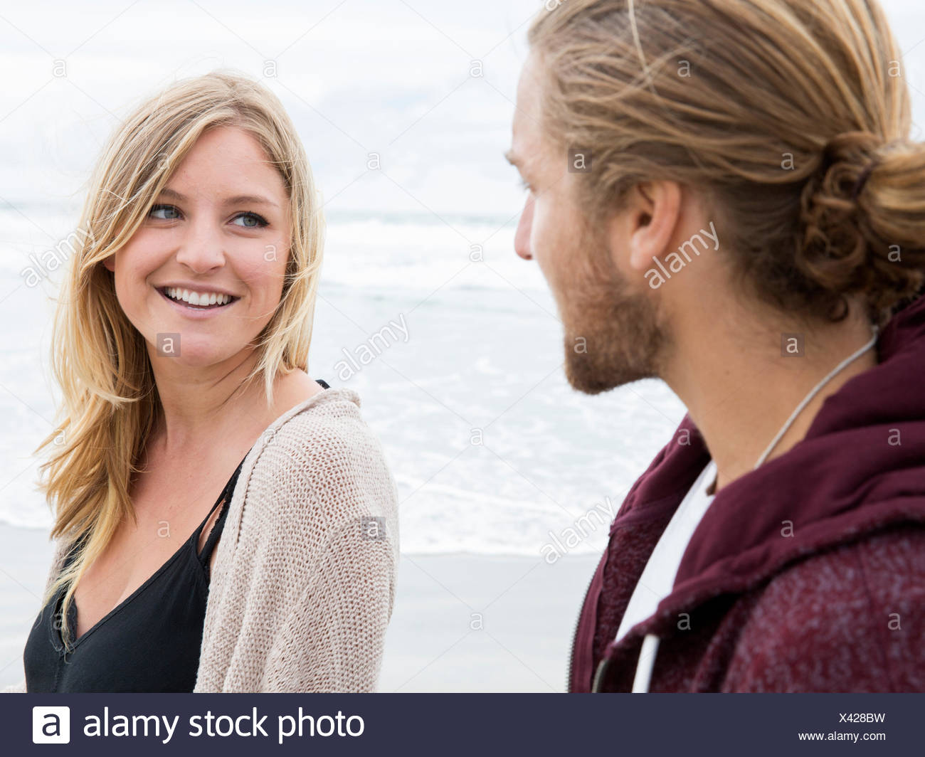 Young man and young woman on a beach, looking at each other, smiling - Stock Image