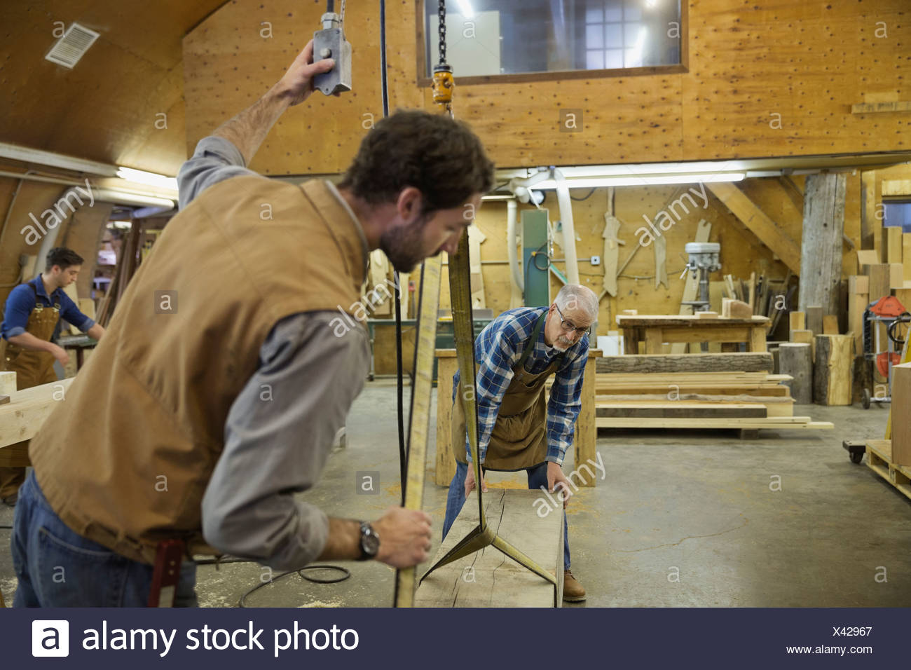 Woodworkers using hoist to move lumber in workshop - Stock Image