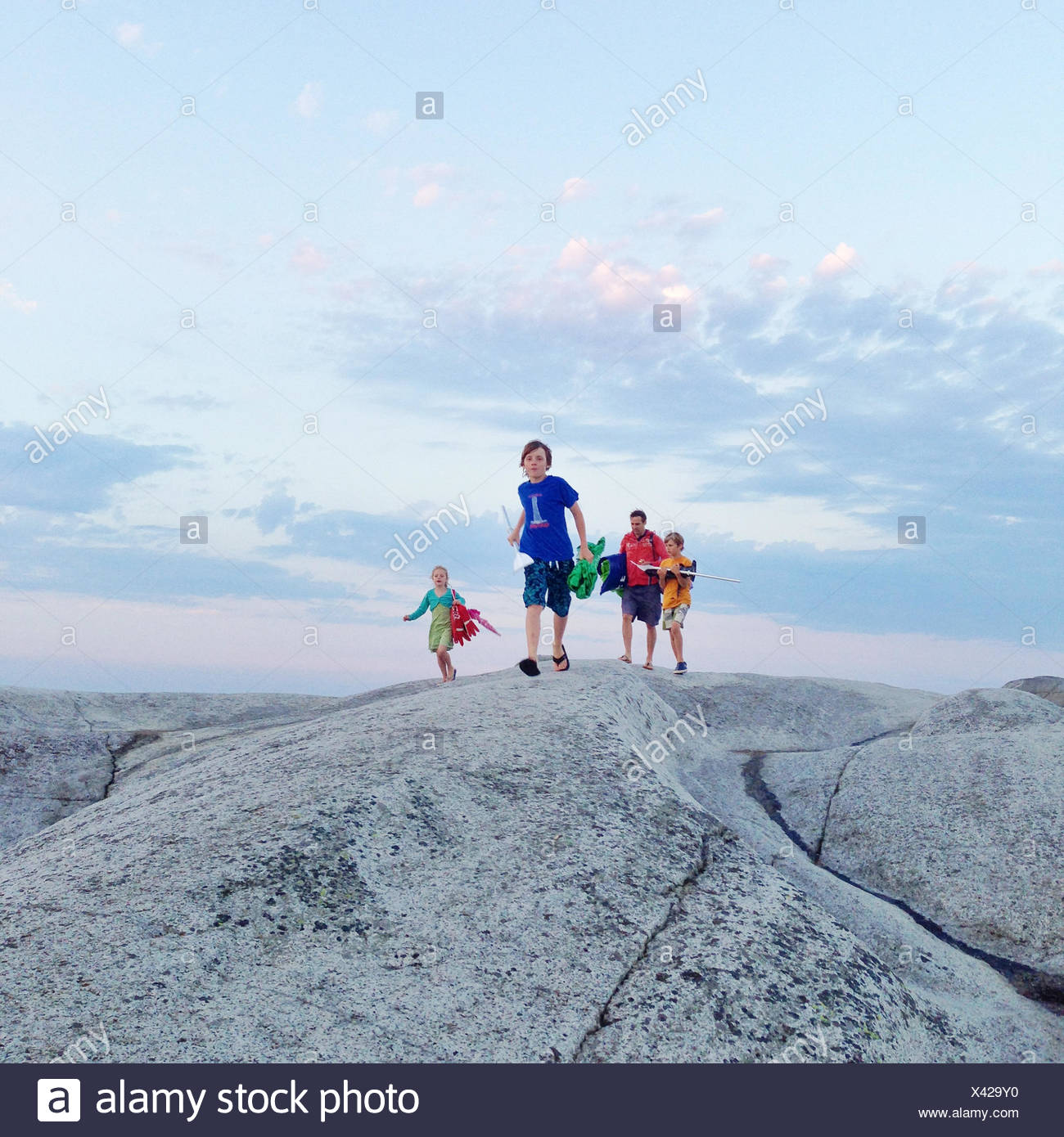 Father with three children walking across rocks, Norway - Stock Image