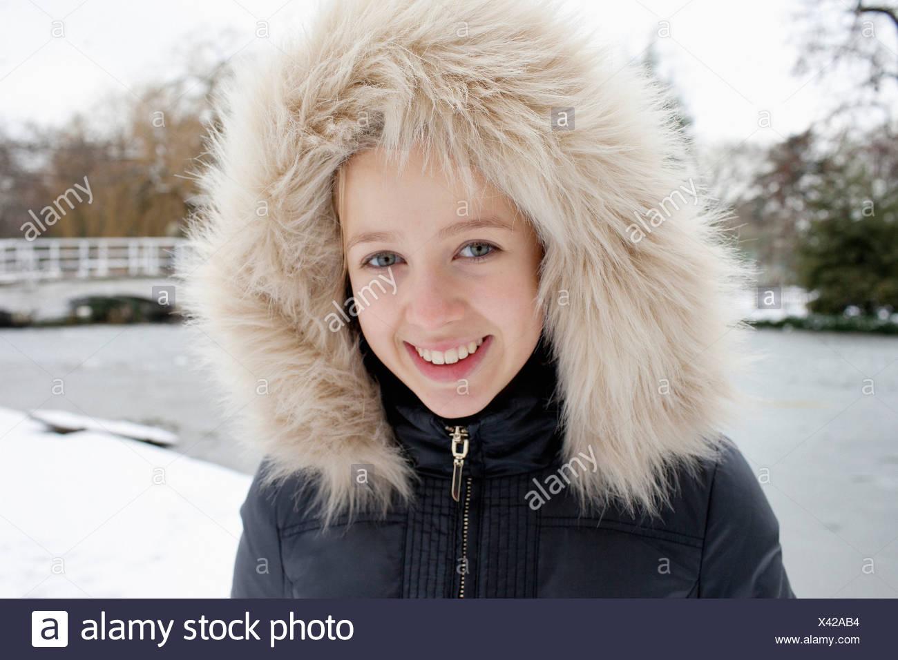 Smiling girl wearing fur hood in snow - Stock Image
