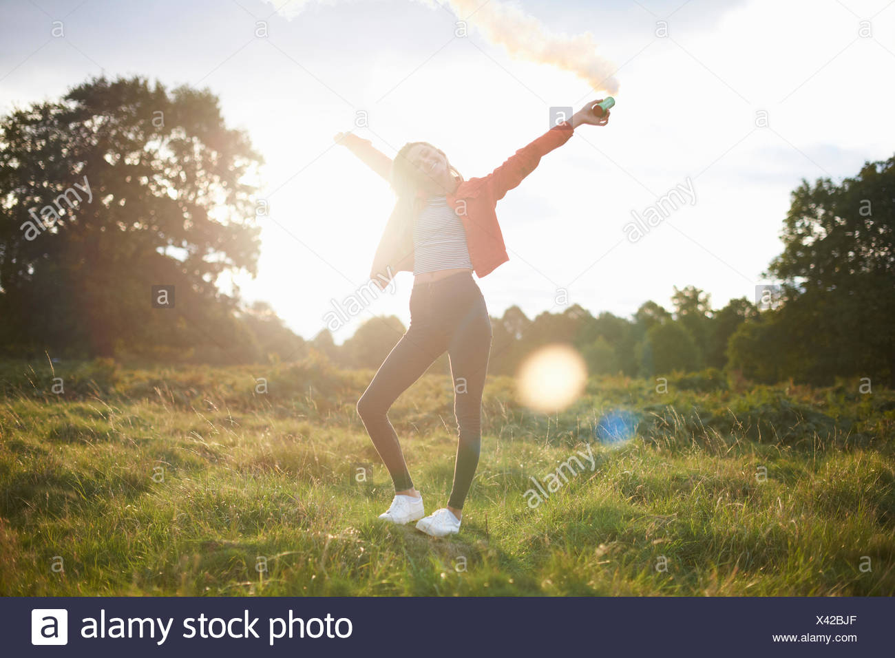 Young woman letting off smoke flare in sunlit field - Stock Image
