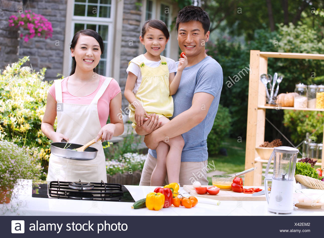 Father held his daughter watched her mother with the cooking - Stock Image