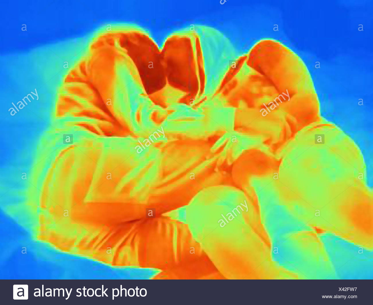 Thermal image of young couple kissing on bed - Stock Image
