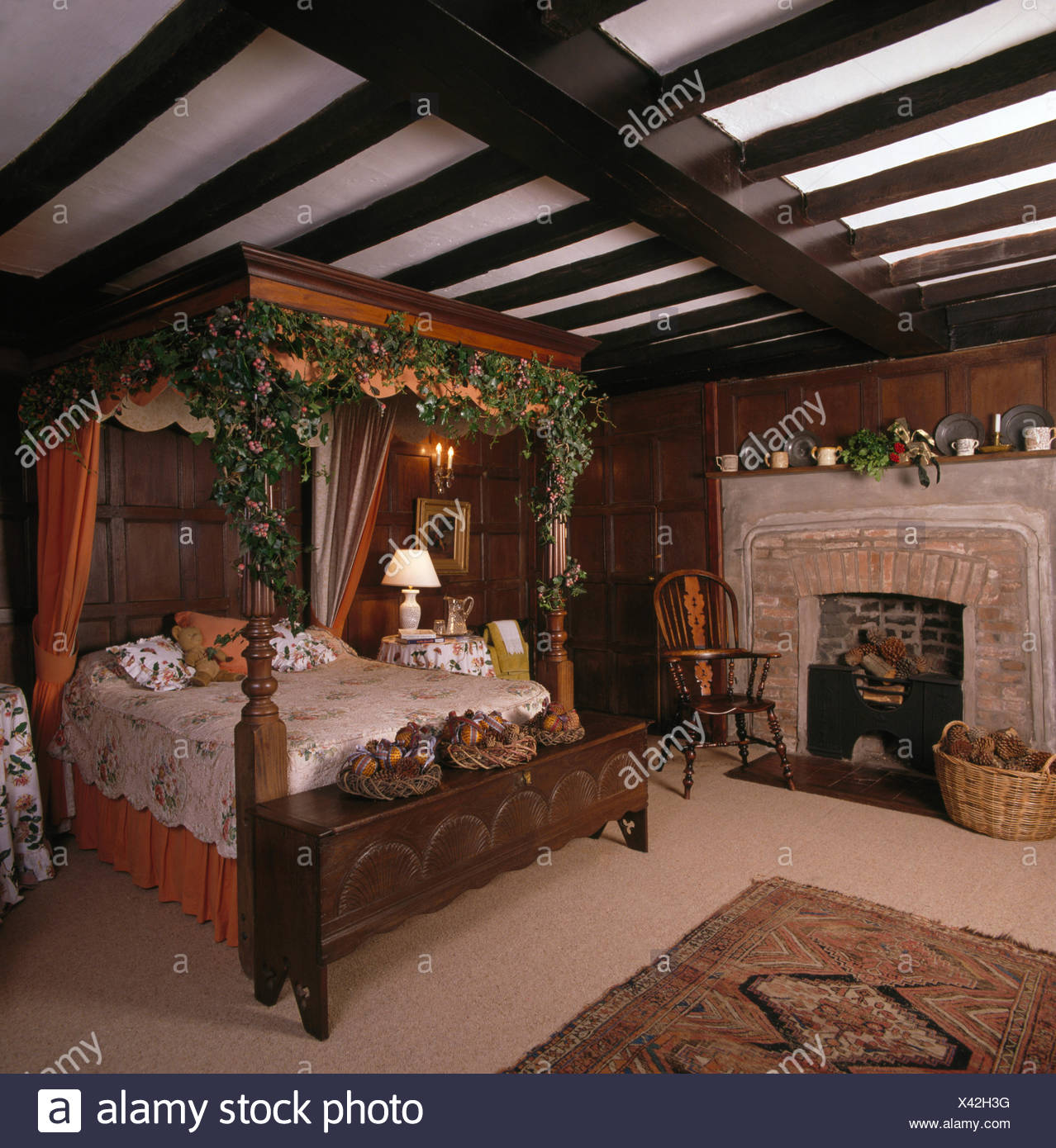 Foliage garland on carved wood four posted bed in beamed country bedroom - Stock Image