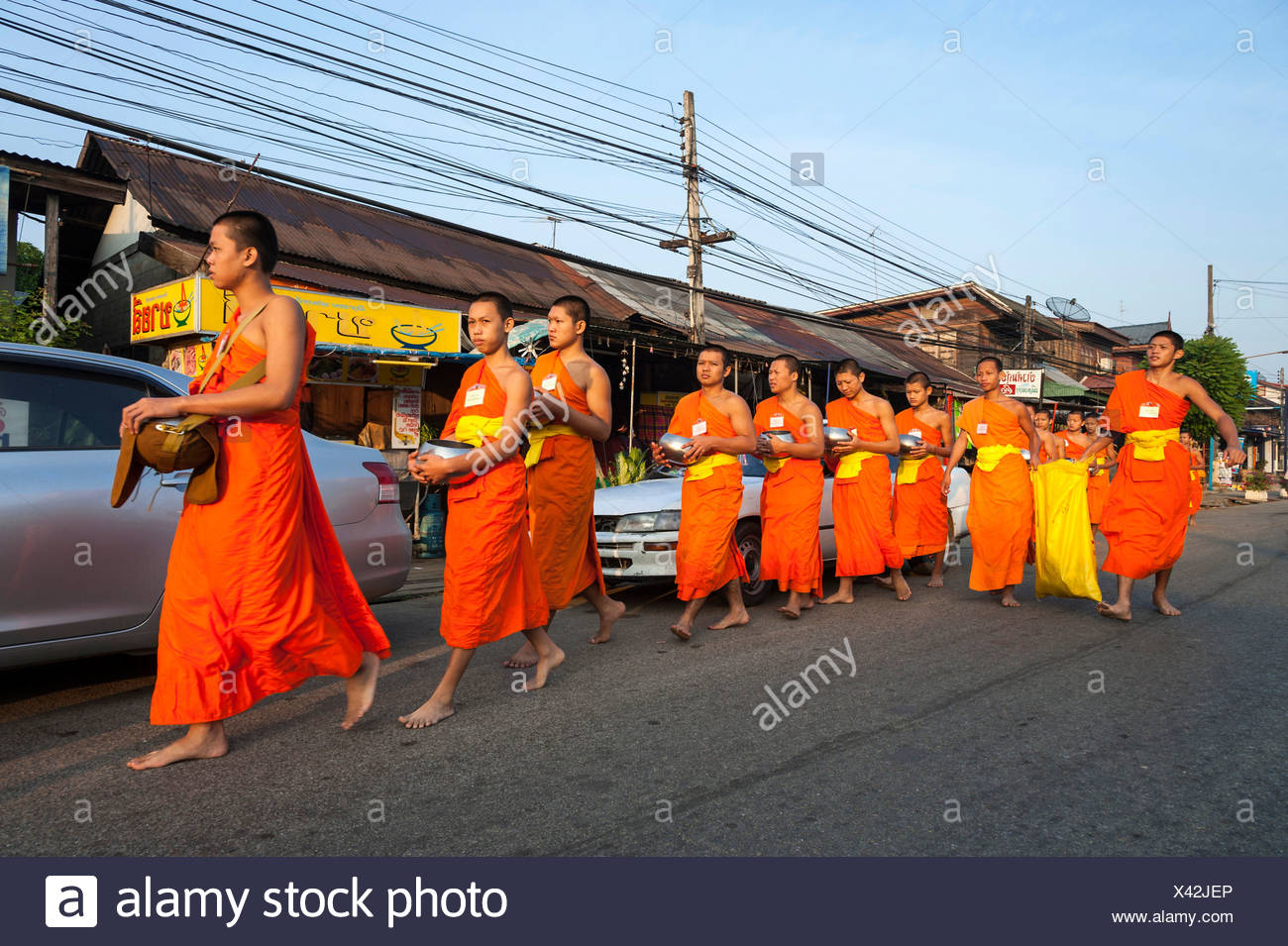 Morning alms round, young Buddhist monks from a monastery school holding begging bowls, Sukhothai Province, Northern Thailand - Stock Image