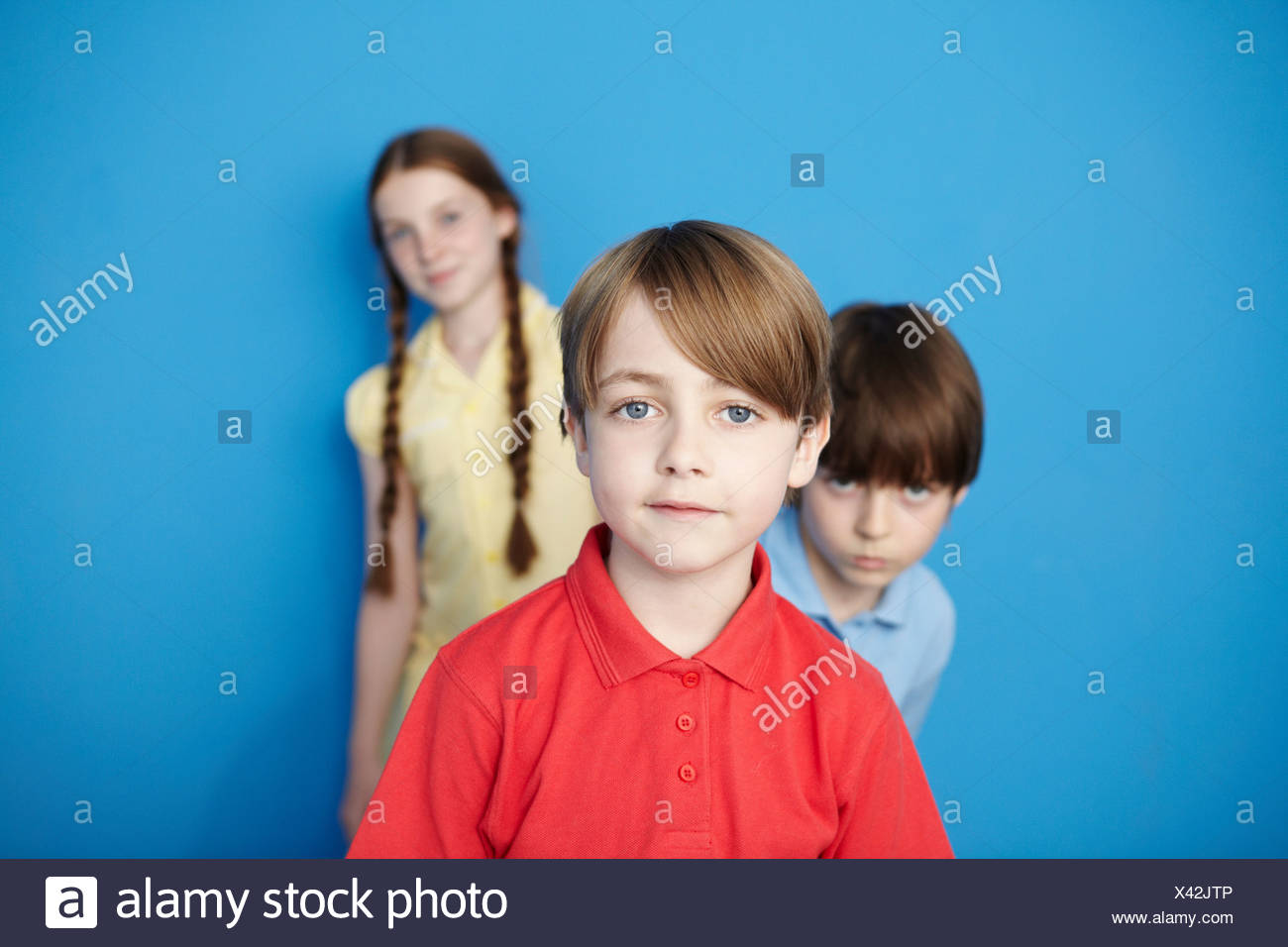 Portrait of three children looking at camera, blue background - Stock Image