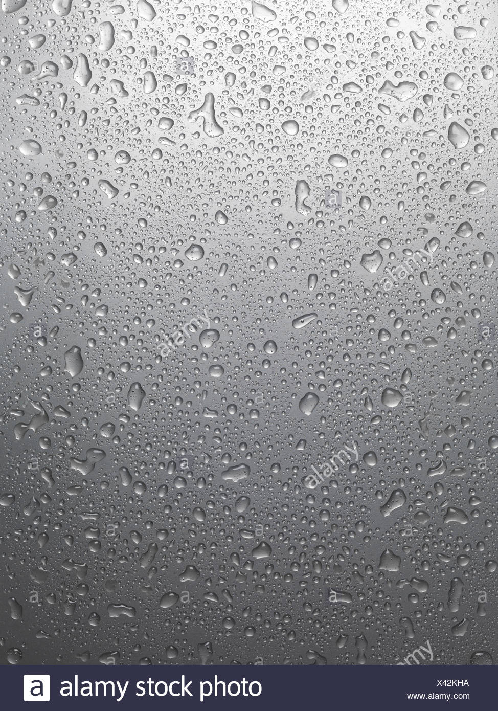 Wet shiny gray metal with drops of water background texture - Stock Image