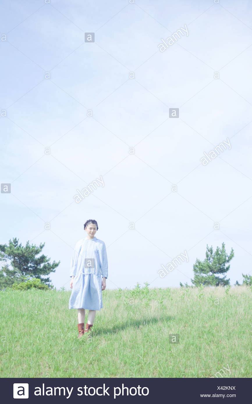 Young woman standing in field - Stock Image