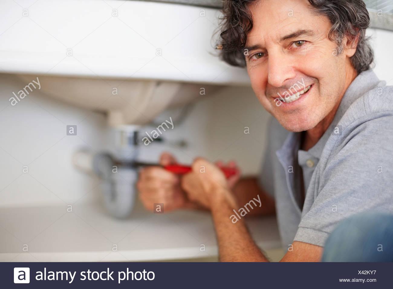 Portrait Plumber Fixing Sink Stock Photos & Portrait Plumber Fixing ...