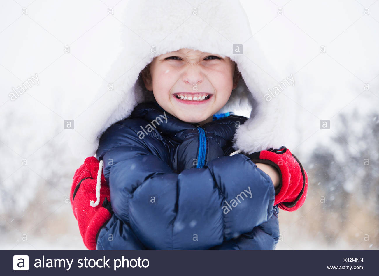 Portrait of boy (6-7) in fur hat and gloves - Stock Image