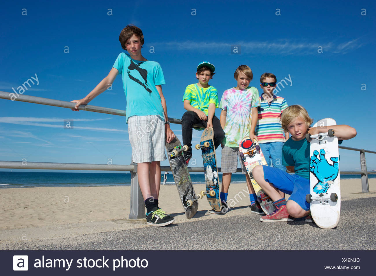 Portrait of five boys with skateboards at coast - Stock Image