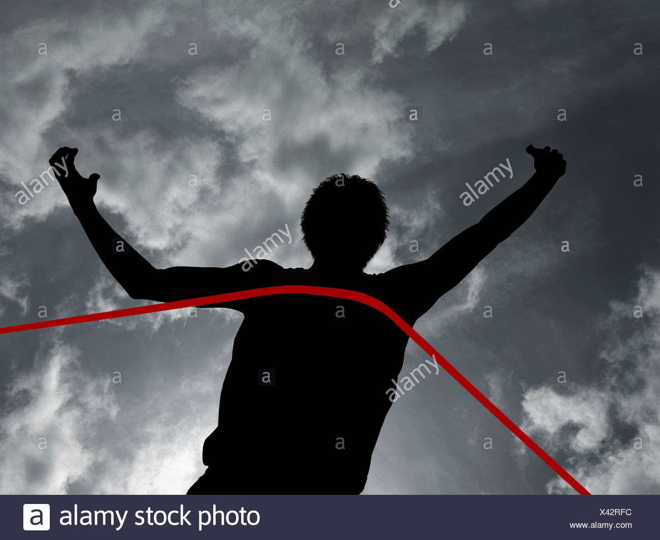 Silhouette of athlete at finish line - Stock Image