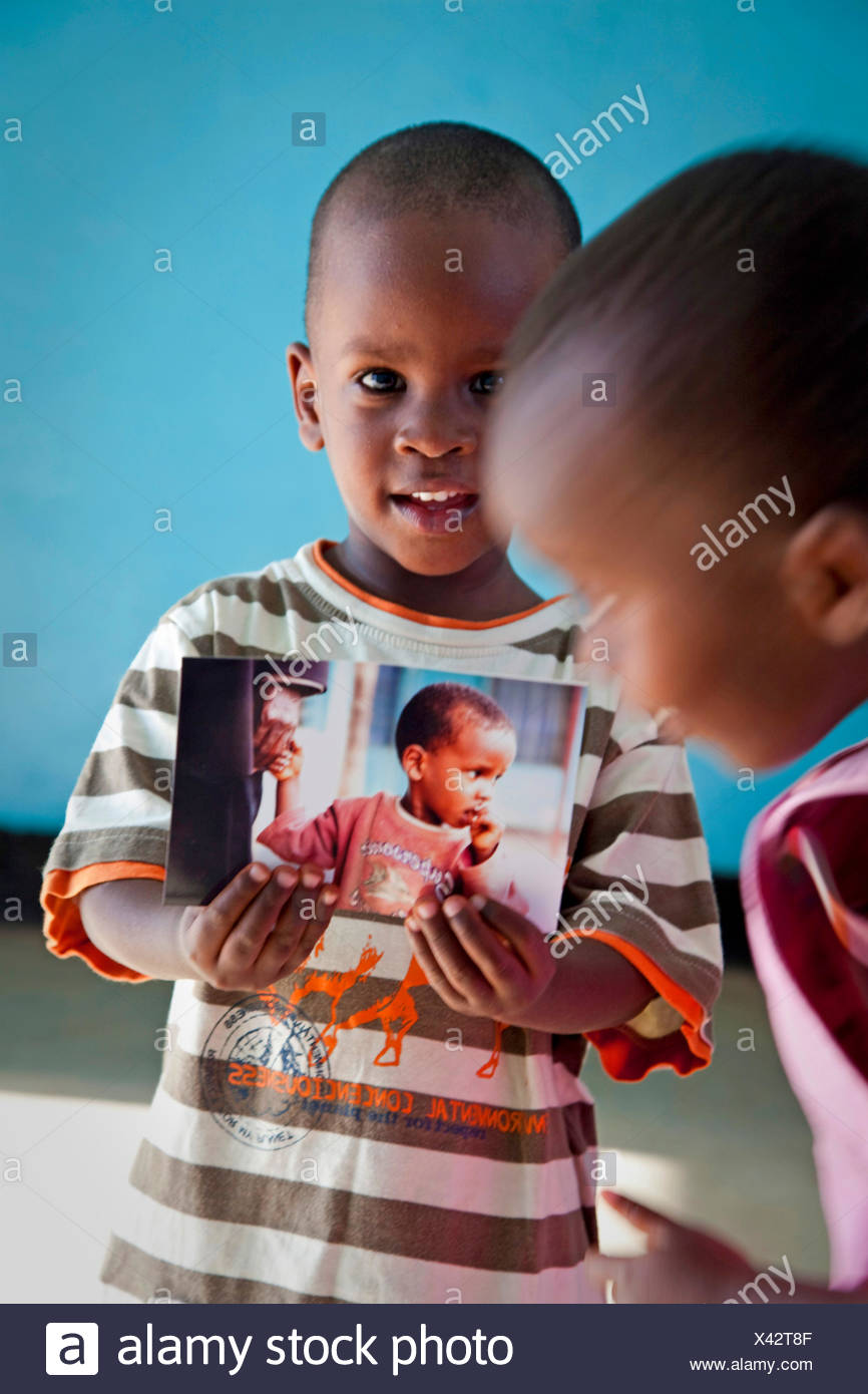 little boy is holding a photograph in hand with himself on it and proudly showing it to a friend, Burundi, Bujumbura Mairie, Bujumbura - Stock Image