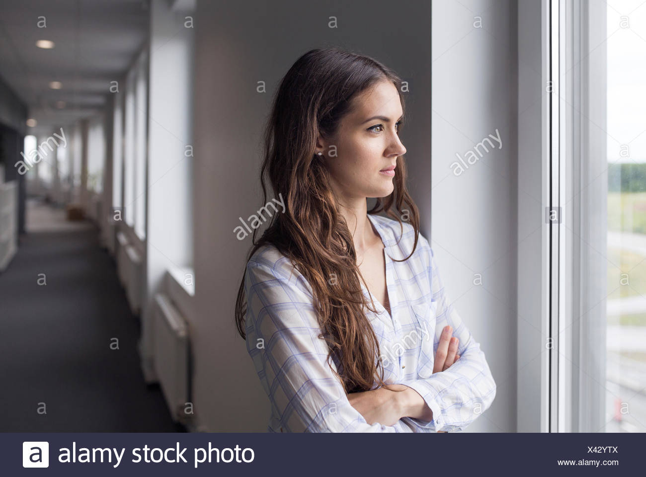 Female architect looking through window - Stock Image