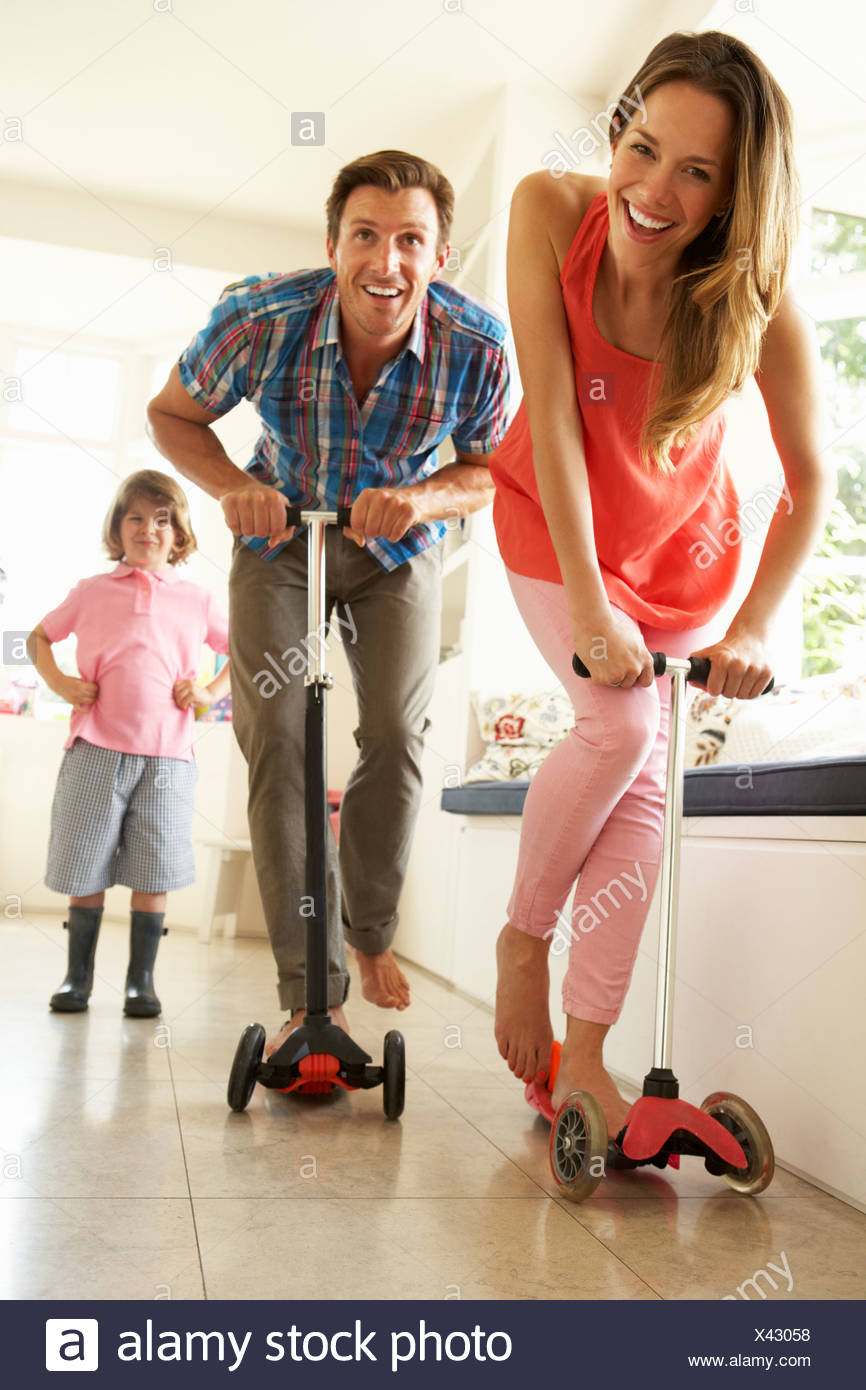 Parents Riding Childrens Scooters Whilst Son Looks On - Stock Image