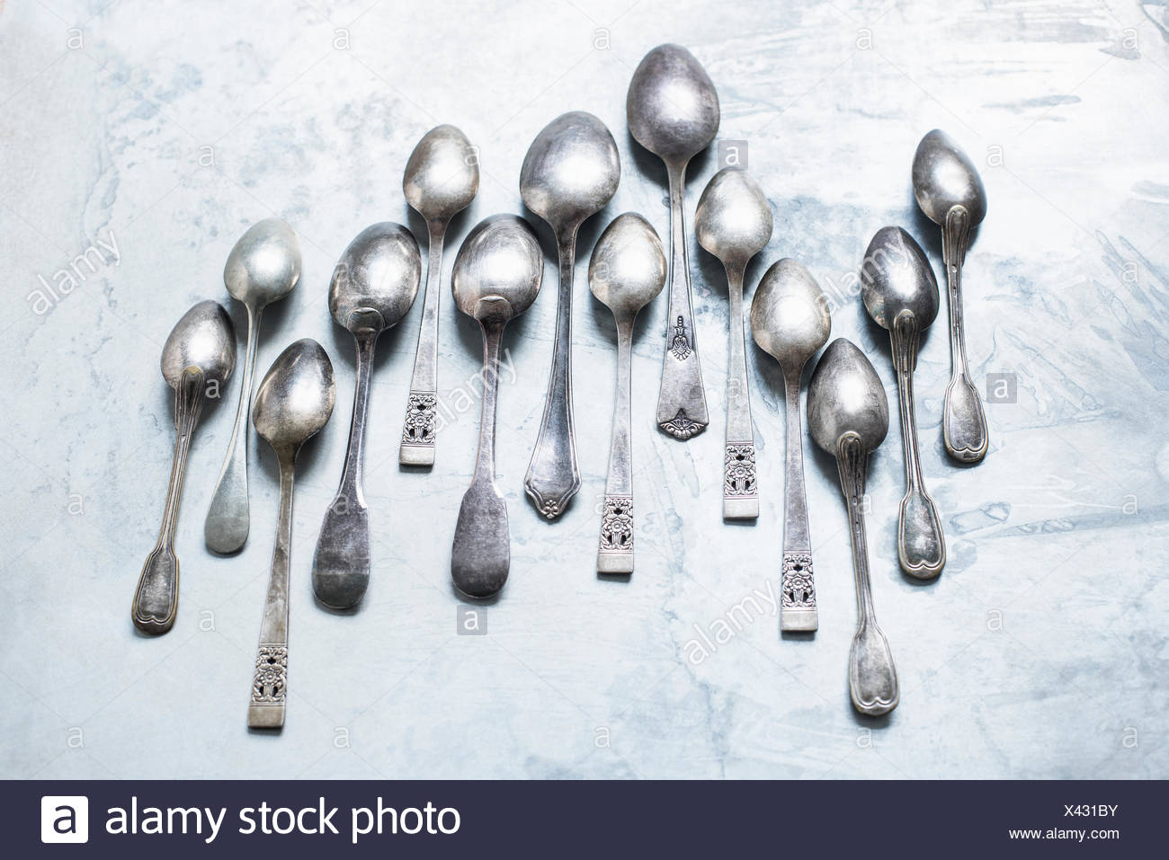 Studio shot, overhead view of teaspoons in staggered row - Stock Image