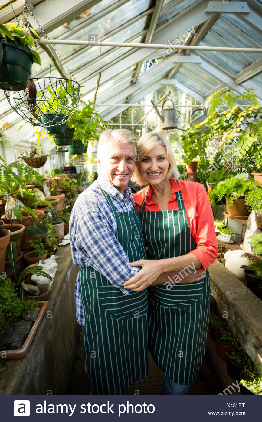 Smiling couple amidst plants at greenhouse - Stock Image