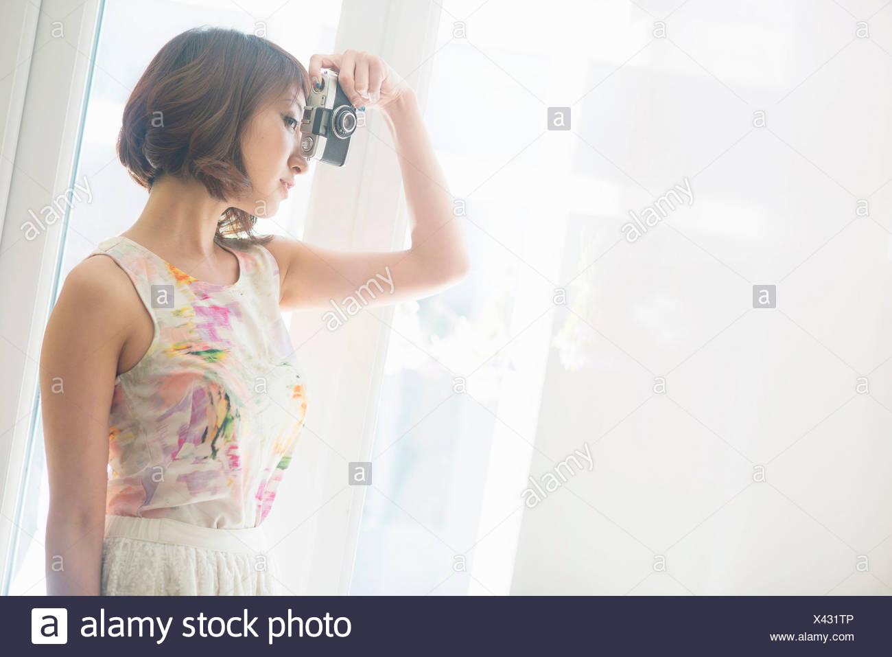 Woman looking through camera - Stock Image