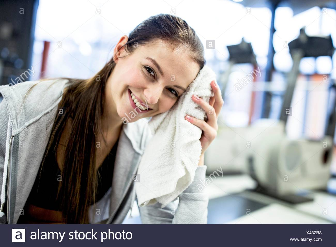 PROPERTY RELEASED. MODEL RELEASED. Portrait young woman wiping her sweat after workout in gym. - Stock Image