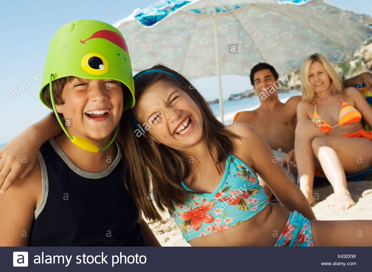 Brother and sister sitting on beach, arm around, boy with bucket on head - Stock Image