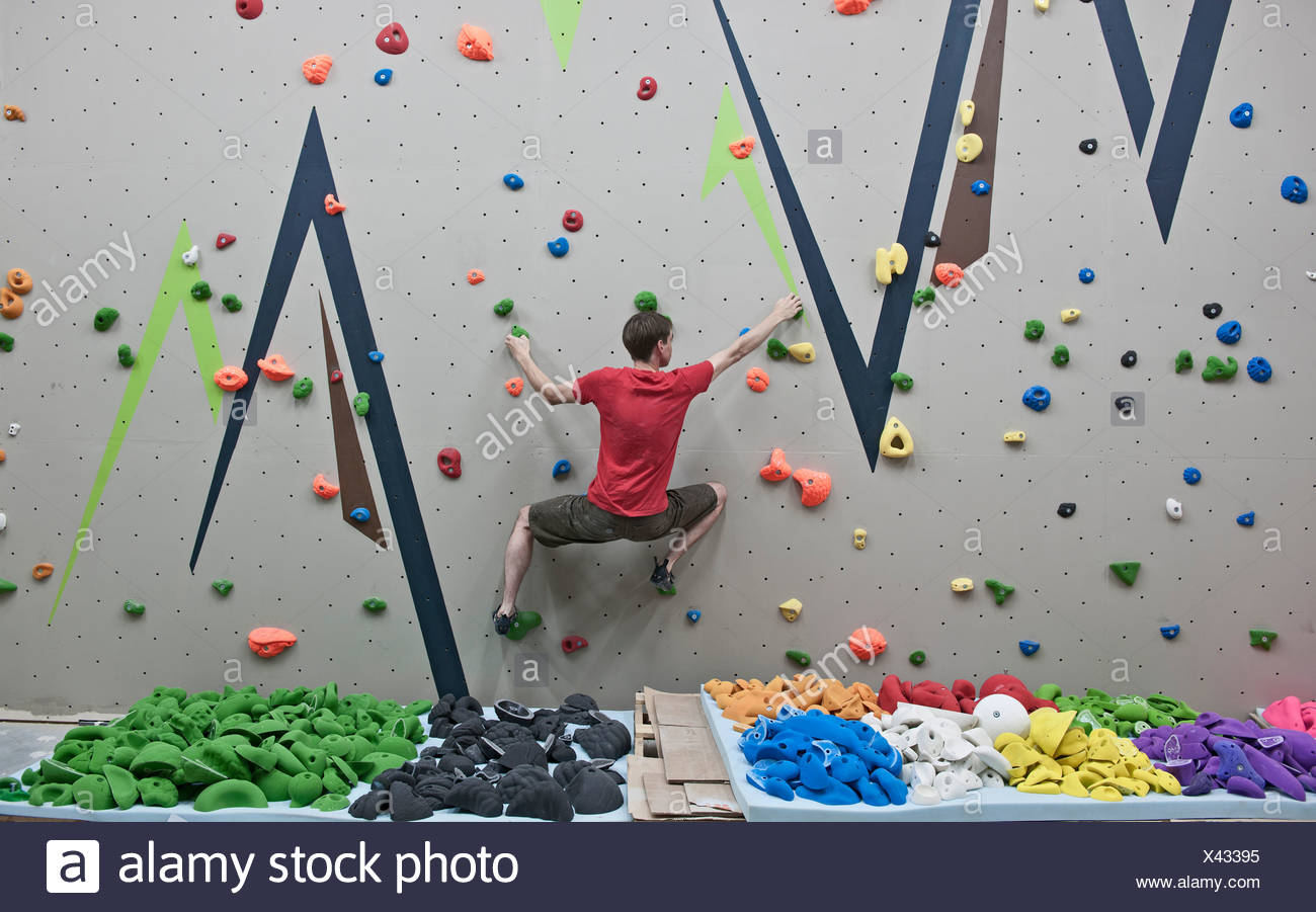 Route setter trying bouldering problem at indoor climbing wall - Stock Image