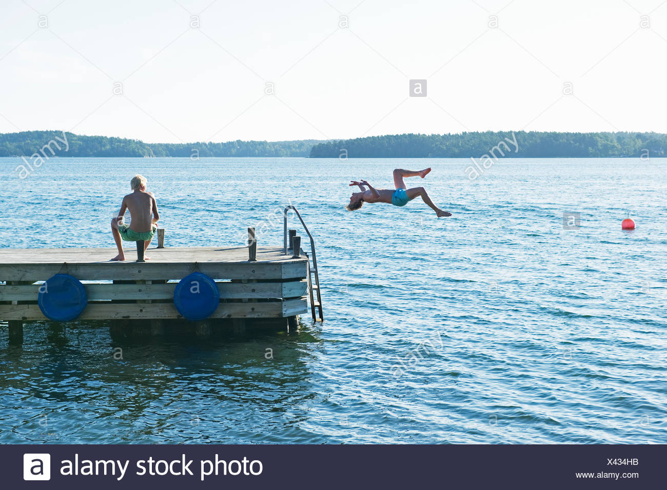 Young man jumping into water from pier - Stock Image