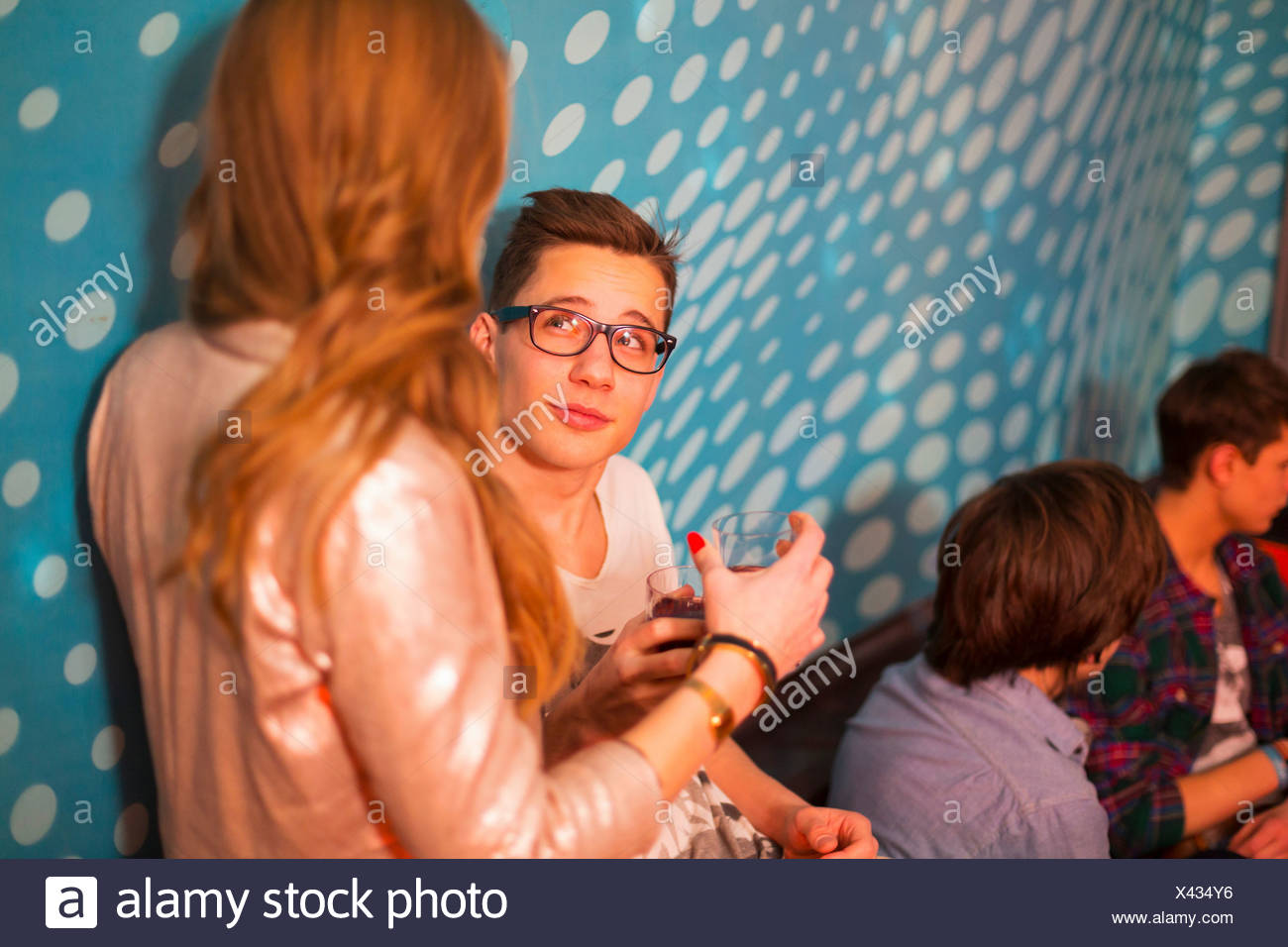 Teenage boy looking up at teenage girl, friends in background - Stock Image