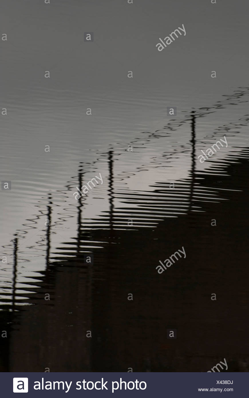 shadow of fence on rippled water - Stock Image